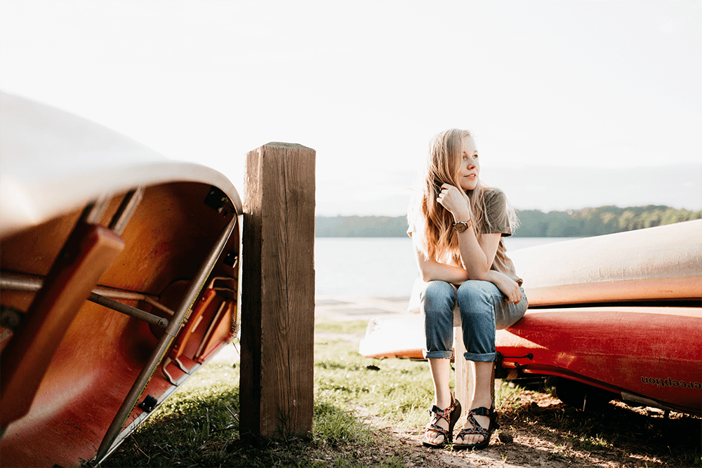 Young expat woman sitting on a canoe on a lake shore